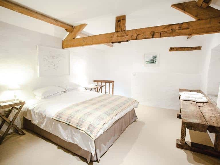 love the modern rustic simple country master bedroom at patrishow farm brecon beacons wales - simple white cotton bedding, welsh wool blanket throws, white washed walls, vintage oak bench table and simple natural flooring. click through to see more lovely shots inside the farm as well as the spectacular local area in the Black Mountains and brecon beacons