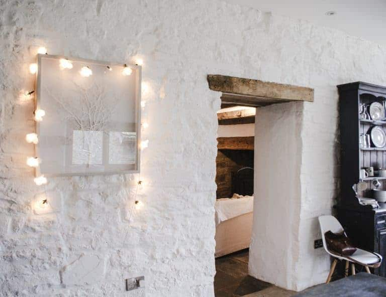 loved this big old stone doorway from the kitchen into the cosy living room at patrishow farm in the brecon beacons wales with old slate flagstone floor, linen covered neutral sofas with welsh wool throws, original oak beams, white washed walls and vintage map prints on the walls. click through to see more lovely shots inside the farm as well as the spectacular local area in the Black Mountains and brecon beacons
