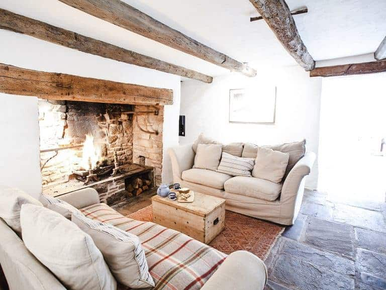 loved the fireplace in the cosy living room at patrishow farm in the brecon beacons wales with old slate flagstone floor, linen covered neutral sofas with welsh wool throws, original oak beams, white washed walls and vintage map prints on the walls. click through to see more lovely shots inside the farm as well as the spectacular local area in the Black Mountains and brecon beacons