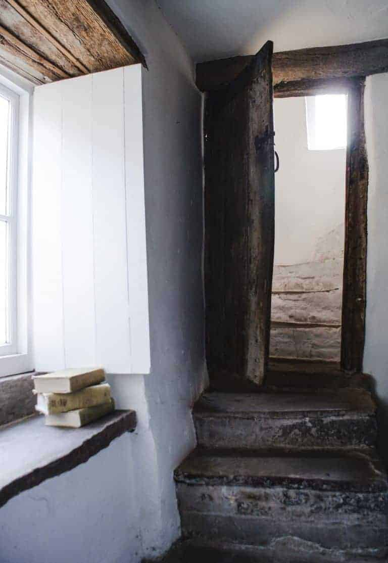 love this modern rustic stone staircase and old welsh cottage doorway at patrishow farm in wales - white washed walls, stone floor, reclaimed wooden units, galvanised metal worktop and butler sink with shelves of vintage and found country objects. This is the perfect dog friendly welsh holiday cottage. Click through to find out more and to see lots of beautiful images from our stay there