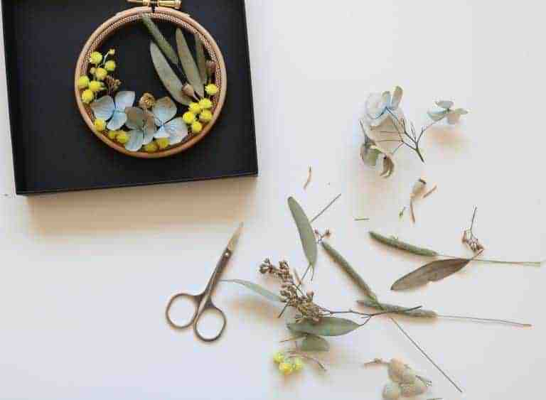 How to make embroidery hoop art with dried flowers. Olga Prinku shares her simple step by step DIY tutorial to create your own mini hoop with hydrangea, eucalyptus, mimosa and spring flowers. Click through for other stunning ideas you'll love to try too #embroideryhoop #embroideryhoopart #driedflowers #frombritainwithlove #olgaprinku #DIY #tutorial #howtomake #embroideryhoopcraft #idaes