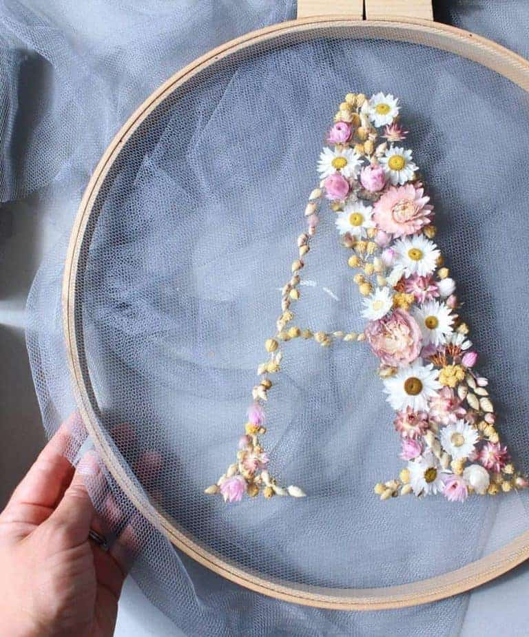 How to make embroidery hoop art with dried flowers. Olga Prinku shares her simple step by step DIY tutorial to create your own alphabet initial hoop with hydrangea, eucalyptus, mimosa and spring flowers. Click through for other stunning ideas you'll love to try too #embroideryhoop #embroideryhoopart #driedflowers #frombritainwithlove #olgaprinku #DIY #tutorial #howtomake #embroideryhoopcraft #iinitial #alphabet