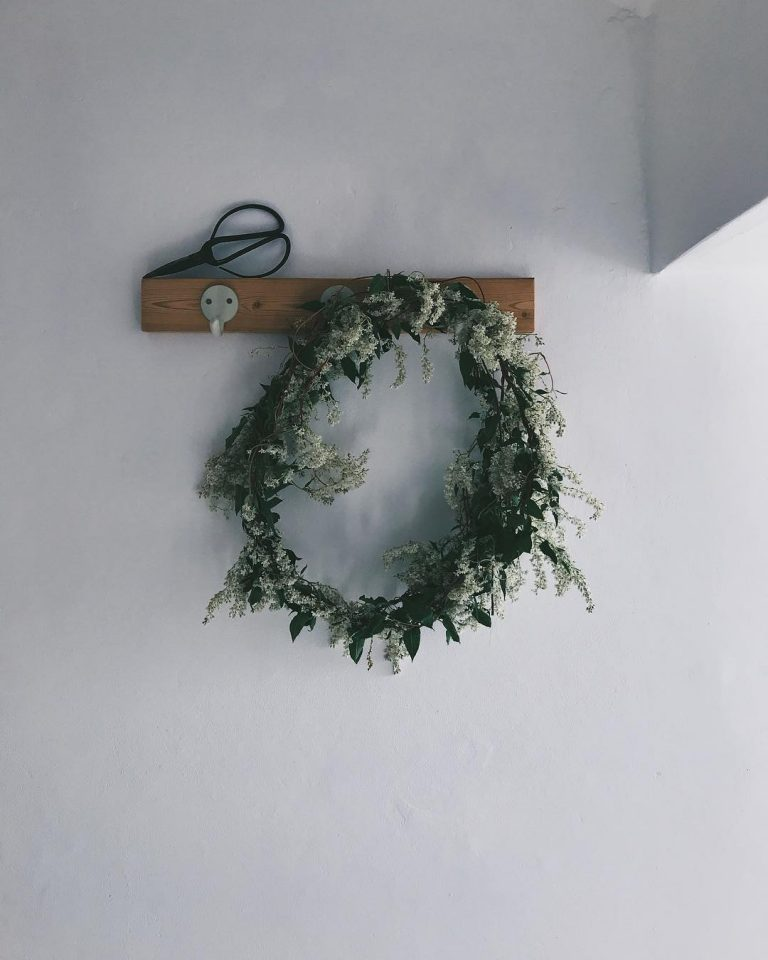 love this instagram photography still life of jug of simple rustic wreath on wooden pegs by laura pashby of circle of pine trees - blogger, photographer and instagram coach. Click through to see lots of inspiring slow living images as well as info on how to get your free ebook how to create engaging content and photography for instagram and beyond #instagram #ebook #slowliving #photography #frombritainwithlove #circleofpinetrees #stilllife #flowers #wreath #woodenpegs