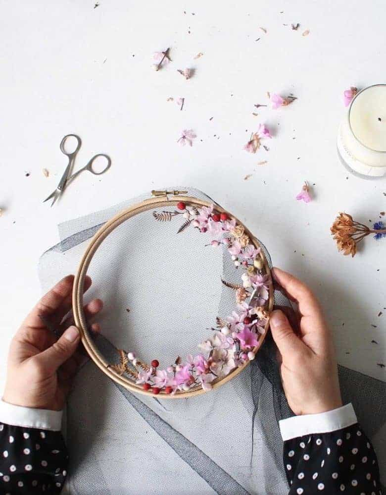 How to make embroidery hoop art with dried flowers and spring blossom. Olga Prinku shares her simple step by step DIY tutorial to create your own botanical hoop art with daisies, cornflowers, mimosa and other dried flowers. Click through for other stunning ideas you'll love to try too #embroideryhoop #embroideryhoopart #driedflowers #frombritainwithlove #olgaprinku#DIY #tutorial #howtomake #embroideryhoopcraft