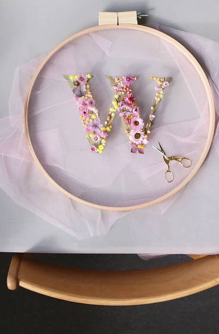 How to make embroidery hoop art with dried flowers. Olga Prinku shares her simple step by step DIY tutorial to create your own botanical hoop art with daisies, cornflowers, ferns, mimosa and other dried flowers. Click through for other stunning ideas you'll love to try too #embroideryhoop #embroideryhoopart #driedflowers #frombritainwithlove #olgaprinku#DIY #tutorial #howtomake #embroideryhoopcraft #initial #alphabet