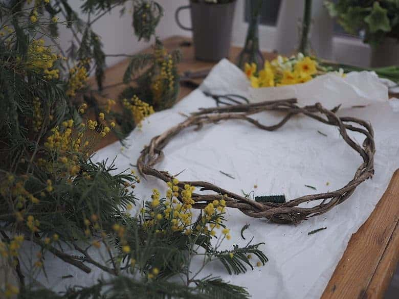 how to make a spring flower wreath for easter - click through for easy step by step tutorial as well as super helpful video guide to making the most beautiful spring flower garland wreath with yellow mimosa, and other easter and spring flowers #springflowers #wreath #easter #easterdecorations #springwreath #frombritainwithlove #flowerideas #wreathideas