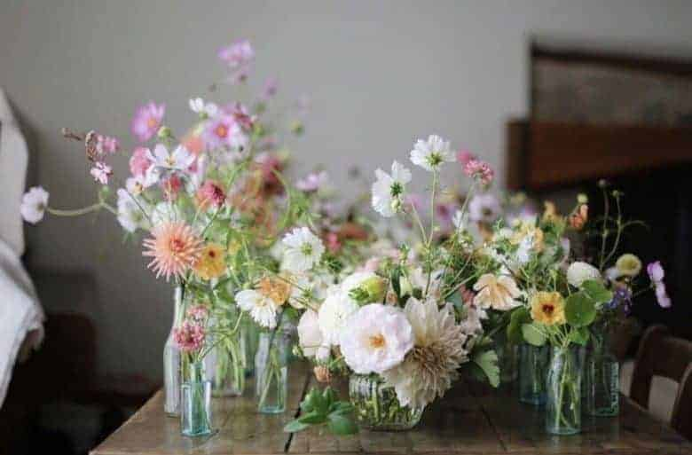 love this collection of glass jars and bottles with pastel wild flowers, dahlias, cosmos table centre arrangement idea. meet Tammy Hall, founder of Wild Bunch flowers - sustainable homegrown british flower farm cutting garden and flower workshops near the welsh border in Shropshire. Click through for all the details you need to connect, book a workshop or find inspiration for summer flower arrangement ideas #sustainable #britishflowers #homegrown #wildflowers #cuttinggarden #frombritainwithlove meet Tammy Hall, founder of Wild Bunch flowers - sustainable homegrown british flower farm cutting garden and flower workshops near the welsh border in Shropshire. Click through for all the details you need to connect, book a workshop or find inspiration #sustainable #britishflowers #homegrown #wildflowers #cuttinggarden #frombritainwithlove #flowerworkshops #flowerarrangements #ideas