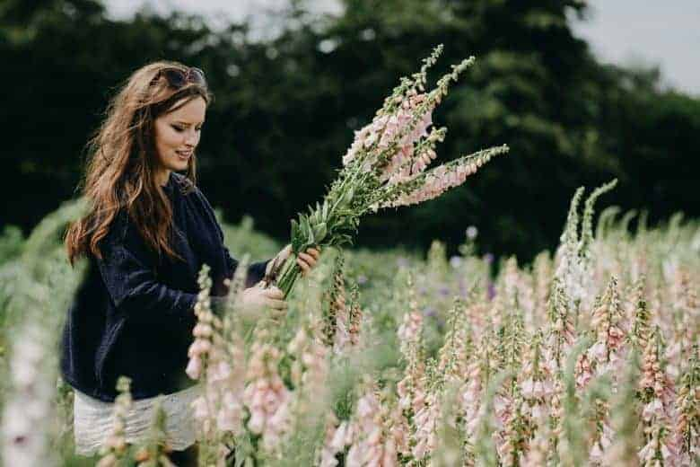 summer meadow flower farm with foxgloves and woman - flower photography tips and ideas from photographer Eva Nemeth including expert tips on how to create depth of field, work with light, texture, aperture and f stops to take beautiful flower and garden photographs #flowerphotography #photography #tips #frombritainwithlove #foxgloves