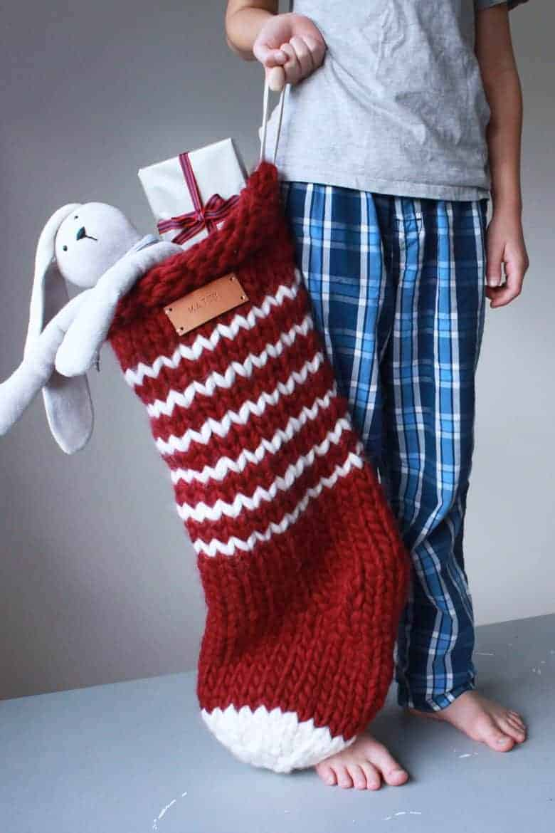how to knit a christmas stocking - love this chunky stripy nordic style stocking in red and white stripes with personalised name tag in leather. Click through for expert tips and links to the perfect knitting pattern #knitting #christmas #stocking #decorations #holiday #craft #tutorial #DIY #knittingpattern #frombritainwithlove