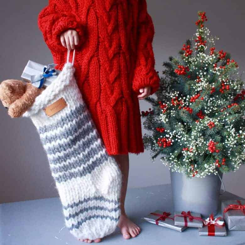 how to knit a christmas stocking - love this chunky stripy nordic style stocking in white with grey stripes with personalised name tag in leather. Click through for expert tips and links to the perfect knitting pattern #knitting #christmas #stocking #decorations #holiday #craft #tutorial #DIY #knittingpattern #frombritainwithlove