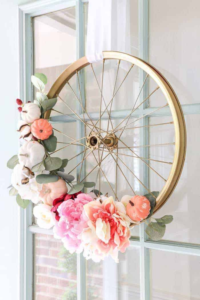 bicycle wheel wreath DIY craft tutorial love this idea for upcycling old wheels and decorating with floral decorations, fresh or artificial flowers etc #wreath #floral #bicyclewheel #frombritainwithlove