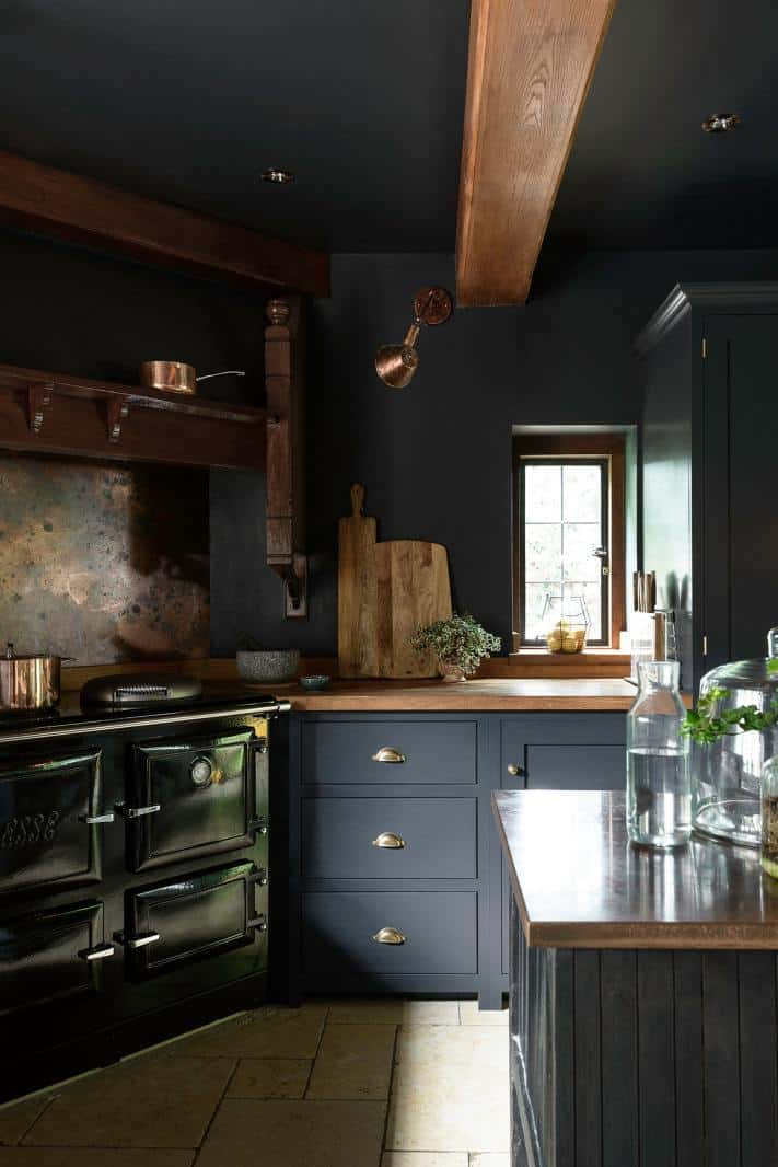 dark kitchen ideas like this Devol kitchen painted in dark, dramatic blue black similar to Railings by farrow and ball with wooden worktops and brass lighting #dark #kitchenideas #railings #farrowandball