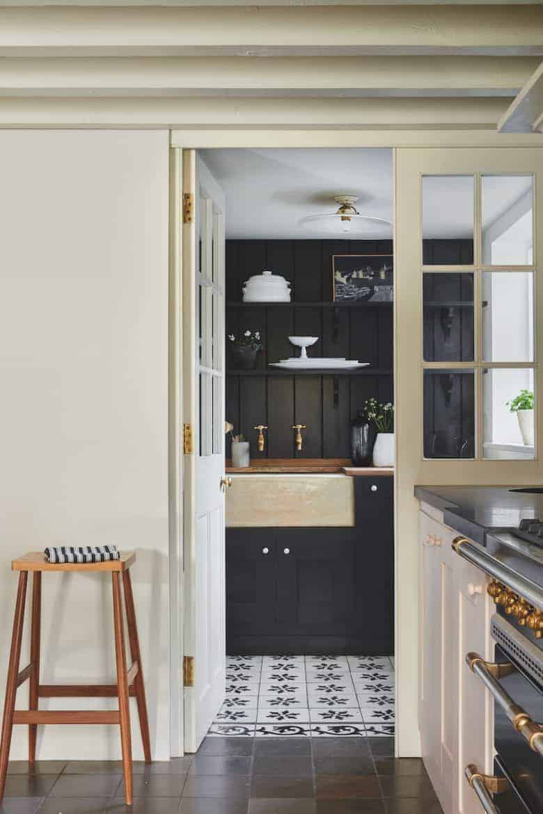 love this rustic dark kitchen painted in Railings by Farrow & Ball, framed by pale doorway and wall painted in School House White paint by Farrow & Ball to create a vintage country modern rustic kitchen feel. Just one of the stunning ideas I've shared #farrowandball #kitchen #rustic #railings #schoolhousewhite #paint #kitchen #modernrustic