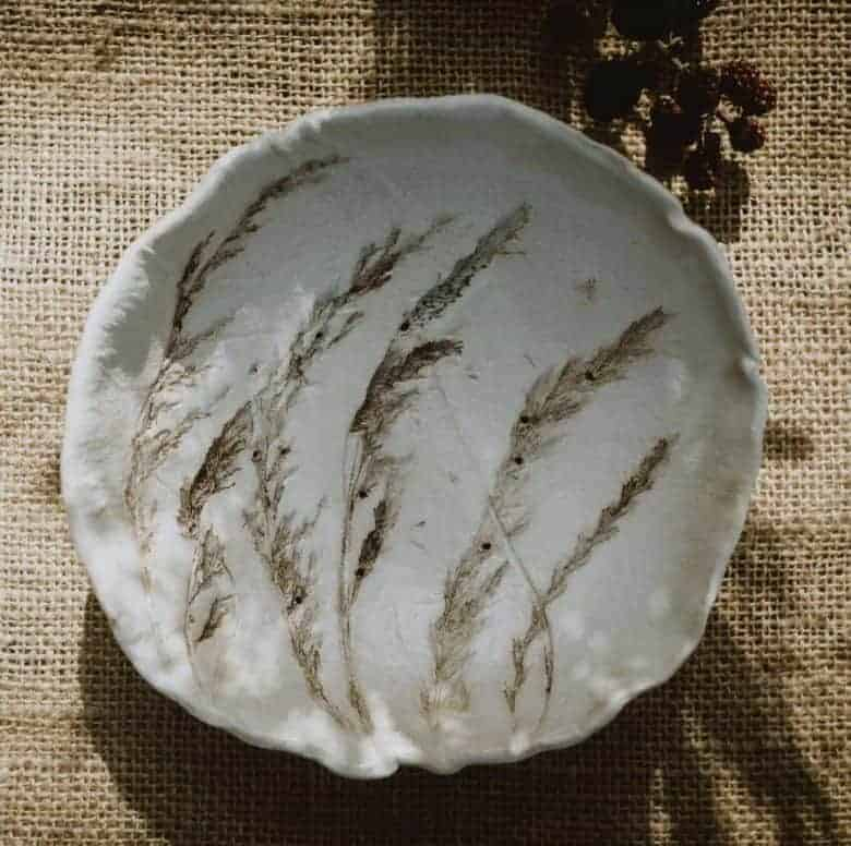 meadow grass print ceramic bowl colander by julie reilly for these to hands - handcrafted in England with the imprint of wild grasses with ruffled edges and glazed with a cream-white and oxides to highlight the pattern in stoneware clay #meadow #grass #ceramic #bowl #colander #juliereilly #handmade