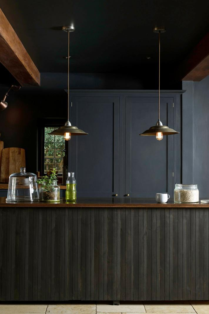 dark kitchen ideas like this Devol kitchen painted in dark, dramatic blue black similar to Railings by farrow and ball with industrial lighting and tongue and groove island with wooden worktops and brass lighting #dark #kitchenideas #railings #farrowandball