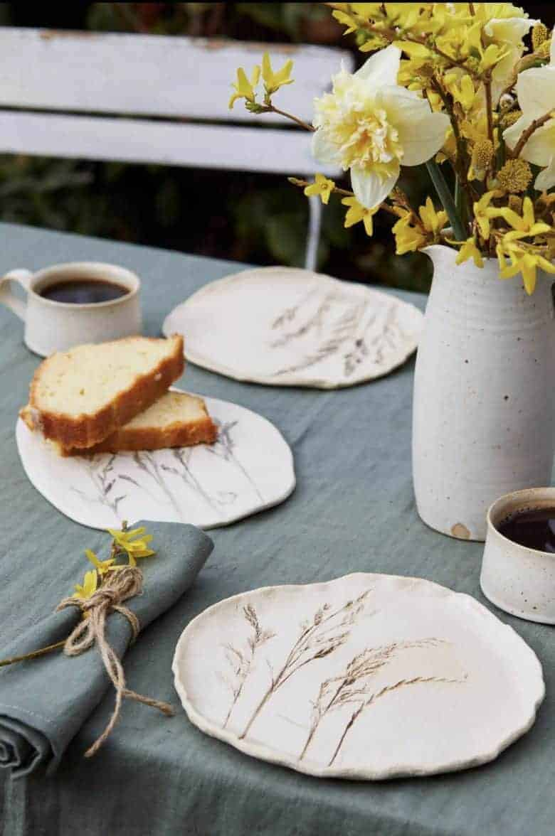 Meadow grass print stoneware ceramic side plates by julie reilly for these two hands handcrafted in England with the imprint of wild grasses with ruffled edges and glazed with a cream-white and oxides to highlight the pattern in stoneware clay #meadow #grass #ceramic #plate #juliereilly #handmade