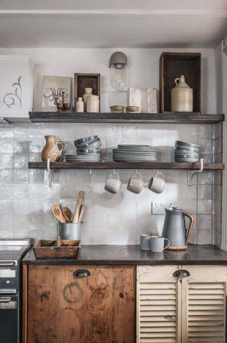 modern rustic kitchen decorating idea - rustic textured white tiles with reclaimed wood open shelves, reclaimed wooden kitchen units, handmade and vintage ceramics, cookware and decorative accessories - just one of the beautiful ideas I've shared, this one from Alba Beach house in St Ives - I've shared all the info you need to book this heavenly haven through Unique Home Stays #modern #rustic #kitchen #decor #ideas #reclaimed