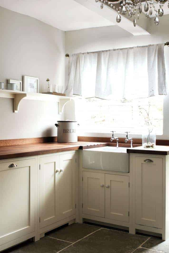 milky white cream paint shaker kitchen ideas with white linen cafe curtains, old vintage shop scales and crystal chandelier with belfast sink and solid wood work tops #kitchenideas #shaker #vintage #white #cream #wood