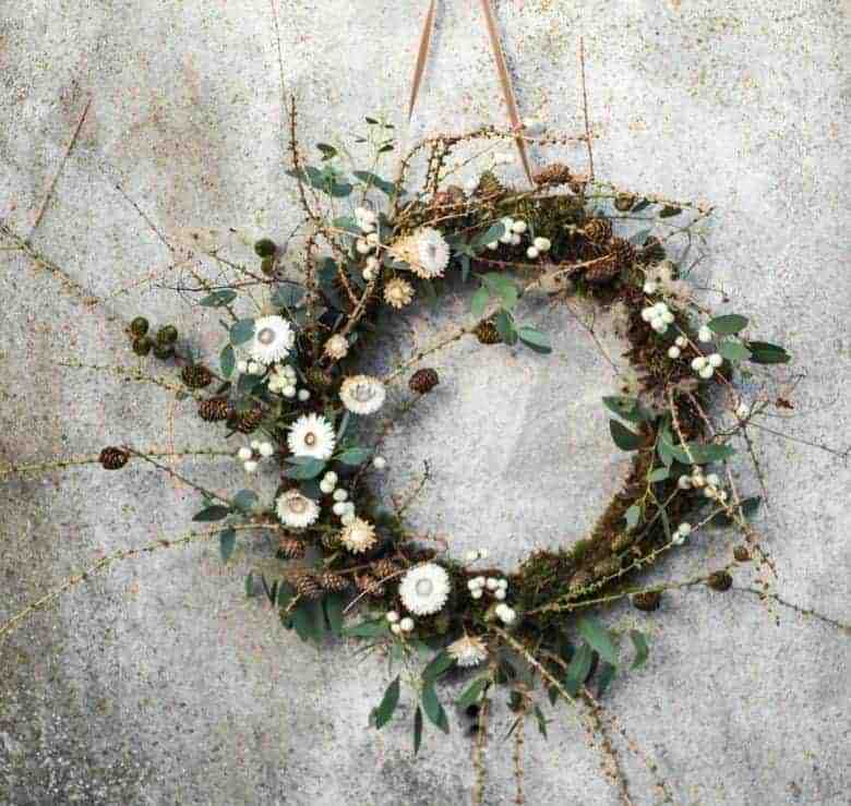 christmas wreath pine cones, foraged twigs, natural foliage eucalyptus and snowberries with dried white flowers helichrysum fresh and dried combined simple natural wreath in green, white and natural wood twigs by green and gorgeous click through for lots more ideas to inspire you as well as simple step by step diy tutorial to make your own wreath for your door #christmaswreath #tutorial #holiday #tutorial #driedflowers #wild