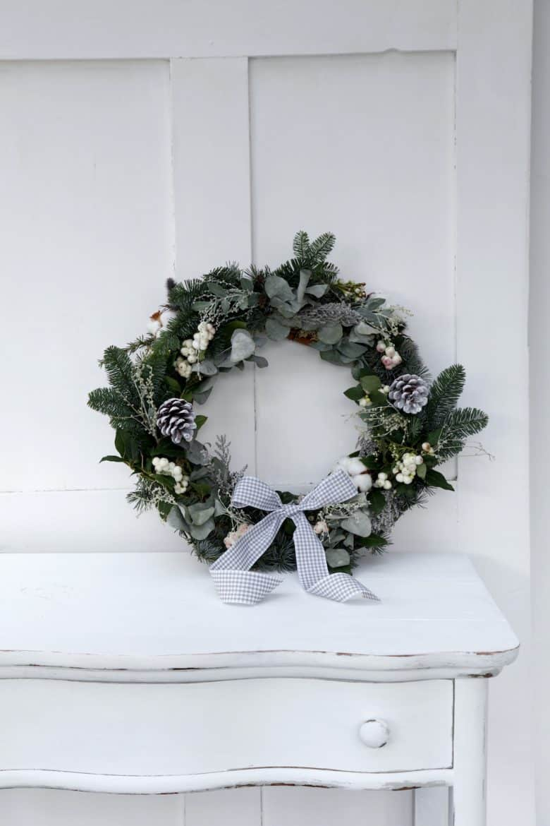 fresh christmas wreath with white snowberries, frosted cones and fresh greenery and evergreen foliage. click through for easy step by steps to create your own christmas wreath with lots more beautiful ideas to inspire you #christmaswreath #christmas #wreath #tutorial #diy