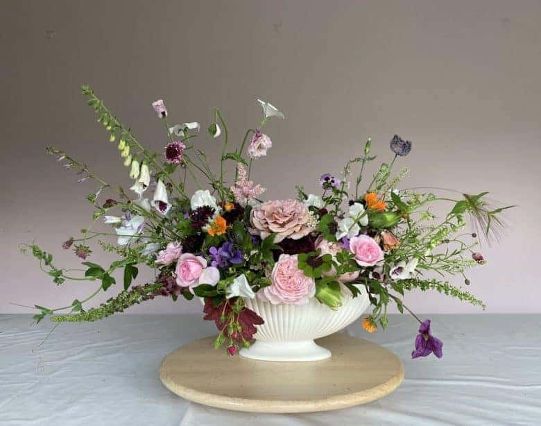 seasonal garden british flowers white urn arrangement roses, foxgloves, sweet peas and pansies
