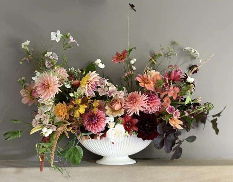 summer flowers white urn arrangement pink and apricot dahlias, snapdragon, amaranthus, snowberries, white wild flowers and seasonal british flowers