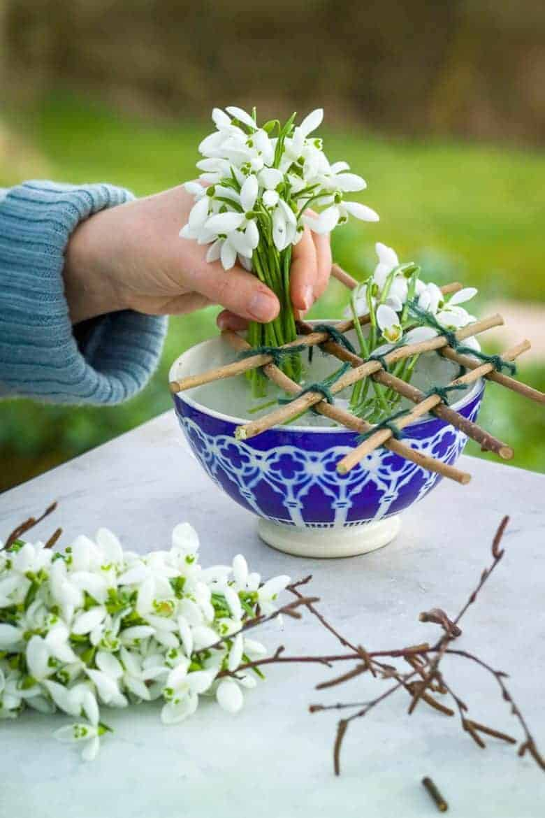 how to arrange snowdrops with Sarah Raven - we share her step by steps to make your own natural flower grid as well as her video tutorial which shows you how to arrange winter and early spring flowers #snowdrops #winter #flowers #flowergrid #sarahraven