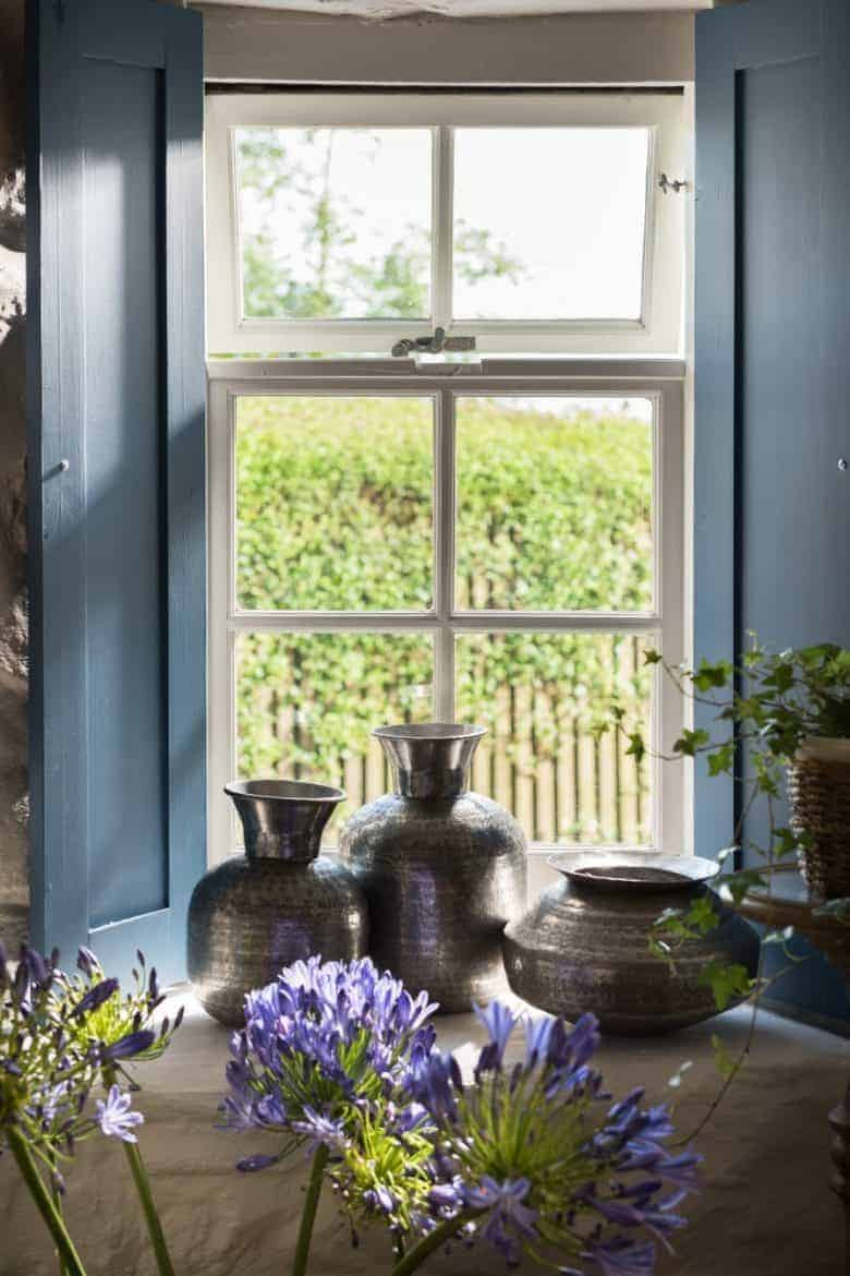 love these blue painted window shutters which work perfectly in a country cottage to frame the garden view #shutters #painted #blue #cottage