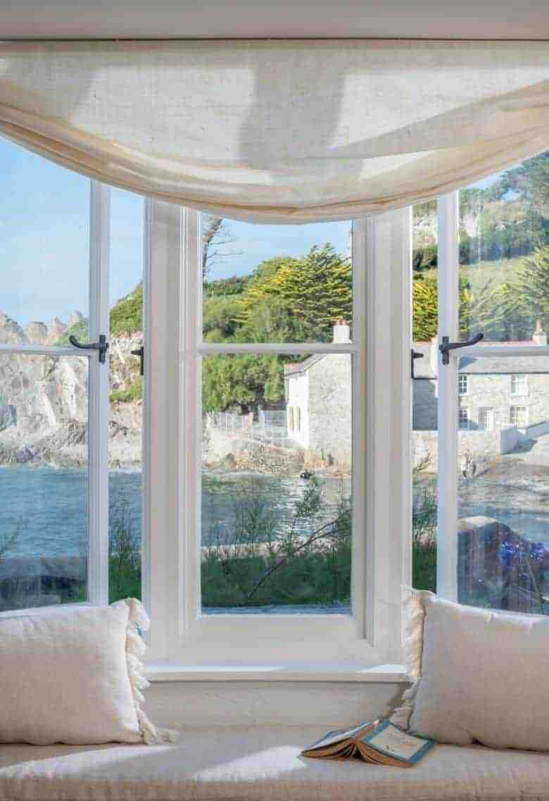 love this window seat with sea view, neutral white linen blind, cushions and old stone walls painted white #cottage #windowseat #seaview