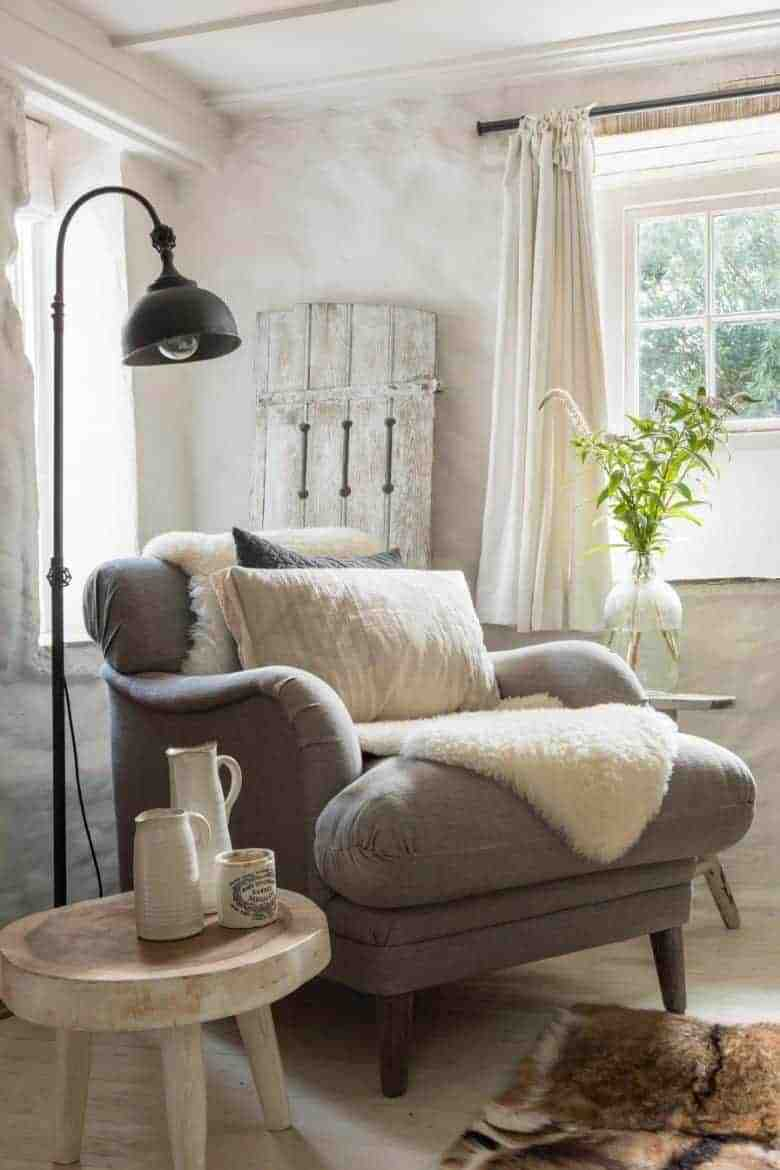 cottage living room soft grey, milky white and neutrals with distressed vintage shutters, grey linen armchair, wooden milking stool, sheepskin and white washed rustic walls and lime white floorboards #cottage #livingroom #grey #white