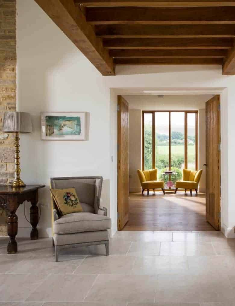 cottage living room hallway with a light airy and modern feel combining pale stone floor white walls, wooden beams and an uncluttered design with bifold doors framing the view of the garden #cottage #livingroom #ideas #decor #inspiration