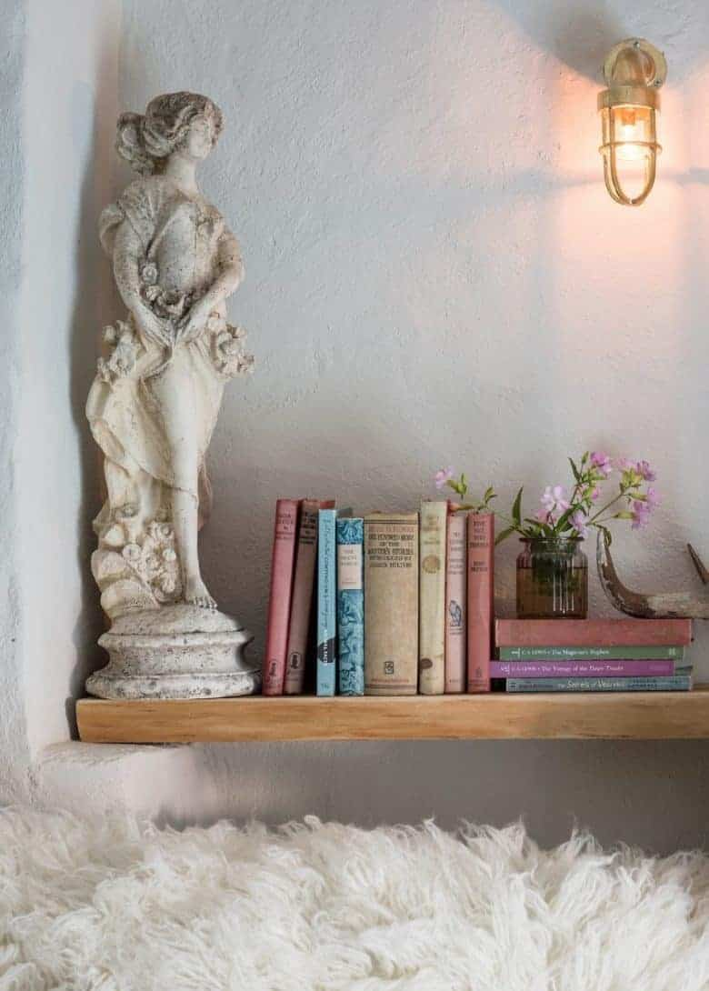 country cottage alcove bookshelf with vintage books, old stone statue, industrial brass wall light and garden wild flowers in a jar #country #cottage #bookshelf #alcove
