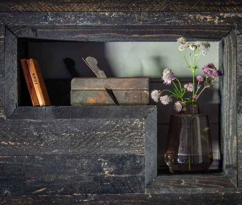 dark wood display alcove with jar of flowers and vintage books