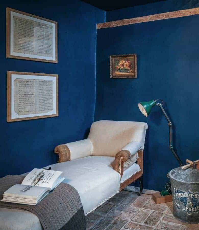 deep blue walls country cottage living room with wooden beams, old brick floor and vintage reupholstered chaise and paintings #blue #cottage #livingroom
