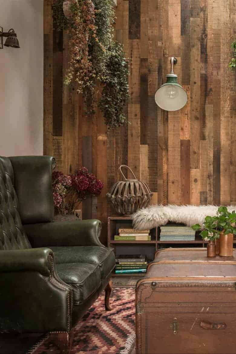 rustic wood panelling living room country cottage with leather arm chair, hanging plants and greenery and industrial lighting #livingroom #cottage #rustic