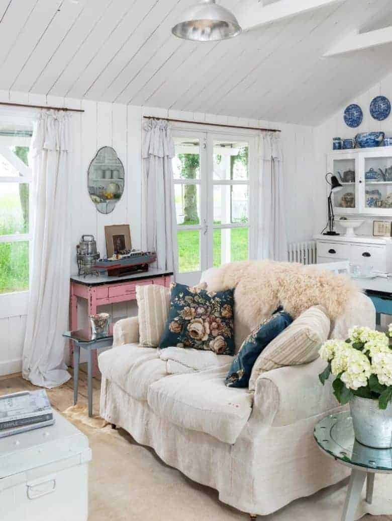 white wash tongue and groove cottage living room with vintage linen slip covers, industrial vintage lighting, vintage mirrors and garden flowers #cottage #white #vintage