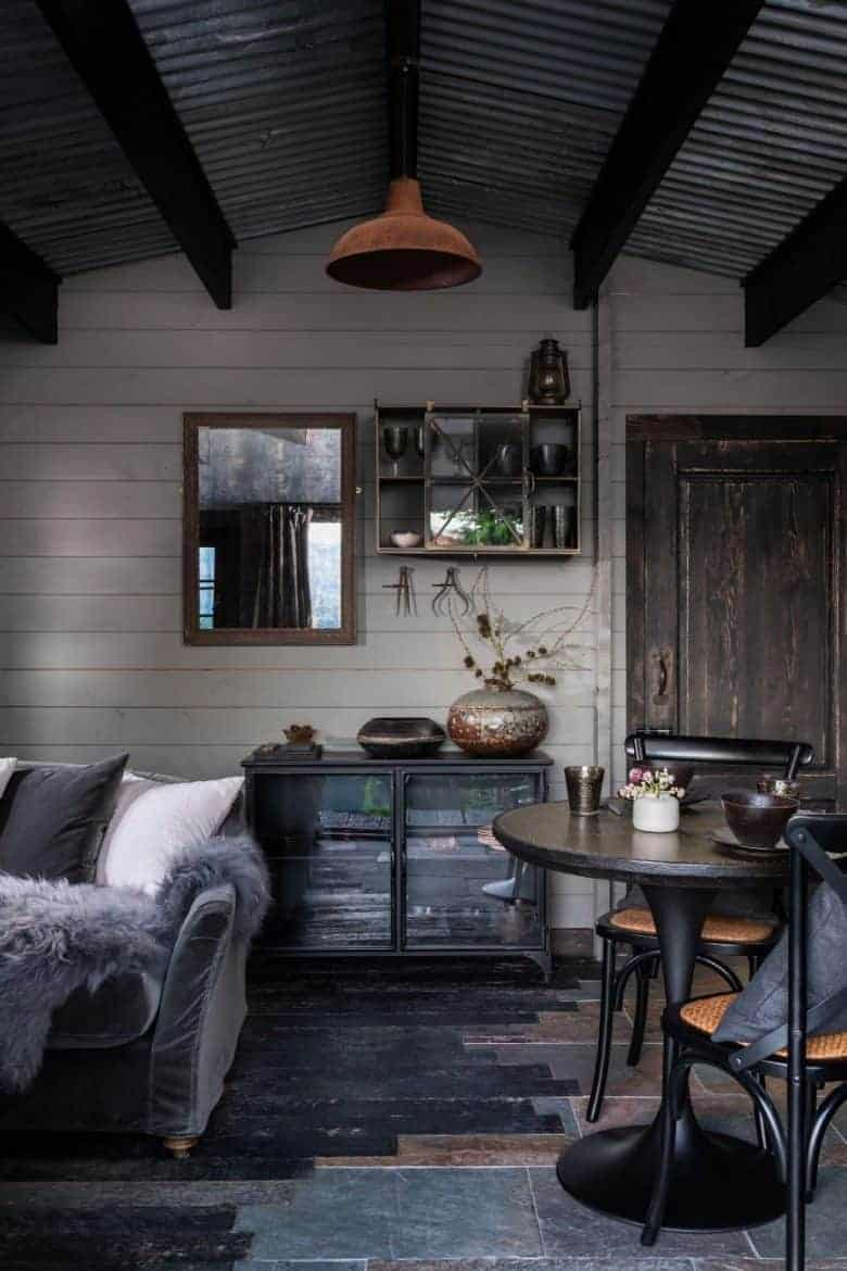love this welsh cottage living room with slate and wood floor, rusted tin light galvanised roof, soft sheepskin and velvet, dark wood and textural ceramics #welsh #cottage #livingroom