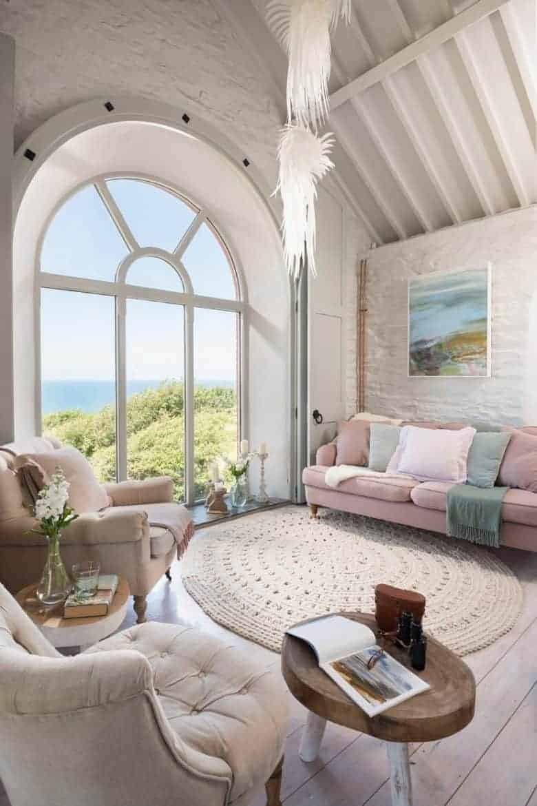 white and pale pink seaside cottage living room with arched window and sea view, white washed walls and floor boards and soft linens and velvet upholstery #cottage #livingroom #seaside