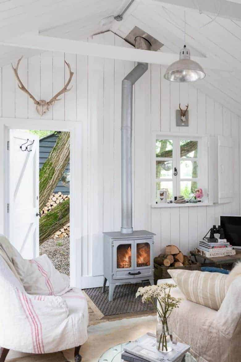 white wash tongue and groove cottage living room with grey woodburner stove, vintage linen slip covers and garden flowers #cottage #white #vintage