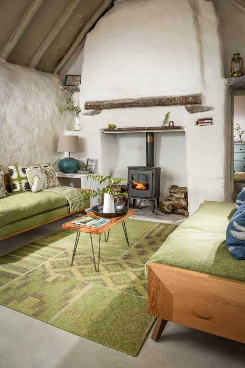 love this cottage living room with whitewashed old walls, oak beams, and midcentury furniture and soft green upholstery and rug #cottage #livingroom #green #whitewash