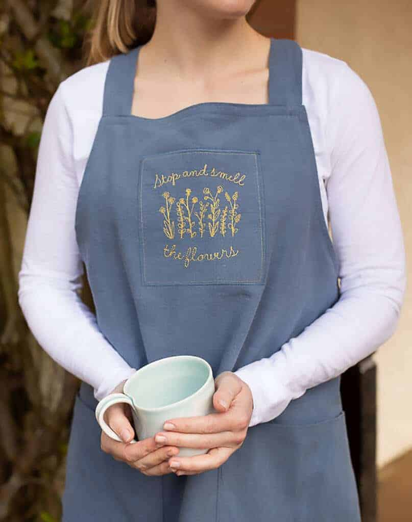 love these embroidered cross back japanese style garden aprons with embroidered flowers and personalised with your name or own choice of words. Handmade by Rudi & Co in Britain in sustainable fabric Ramie which is like cotton but feels more like linen #apron #linen #sustainable #handmade #embroidered #flowers