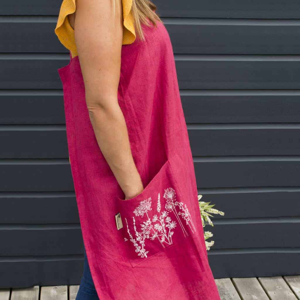 Love this bright pink linen apron made in cornwall by Helen Round with hand printed garden flowers design on the pocket and cross back japanese apron style #linen #apron #pink #flowers