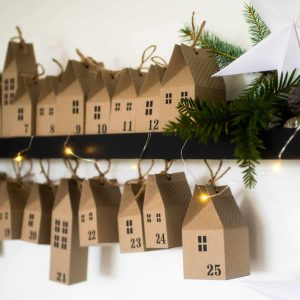 make your own diy advent calendar village little brown paper houses tied up with string
