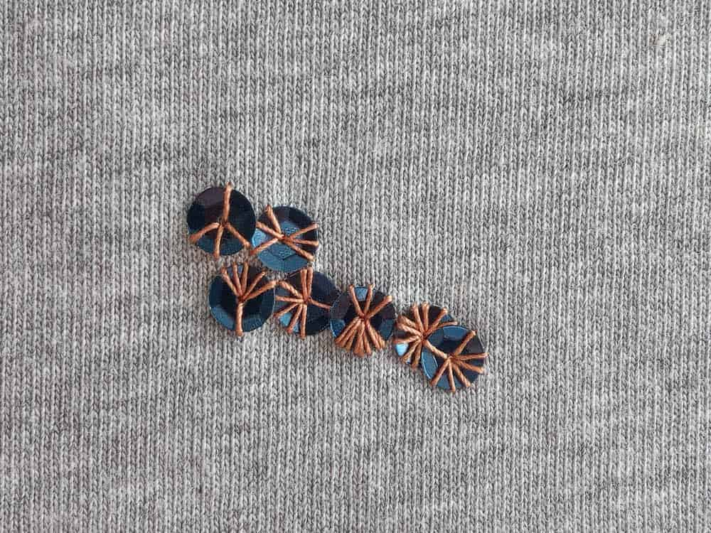 repair knitwear with sequins moth hole repair blue sequins with contrasting thread
